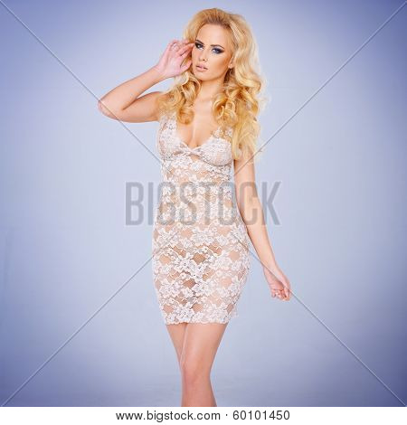 Glamorous young blond woman with a shapely figure in a sexy see-through lacy white dress against a blue-grey background