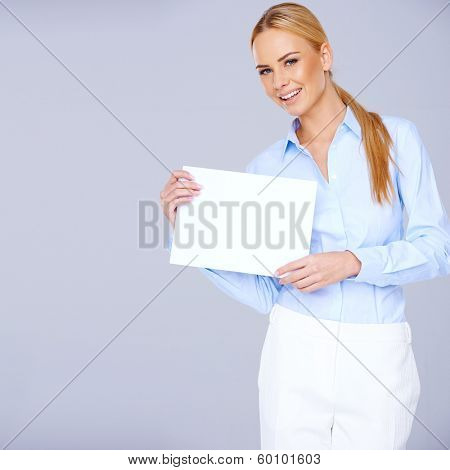 Beautiful elegant blond woman with long hair standing holding a blank white sign in her hands on a blue-grey background