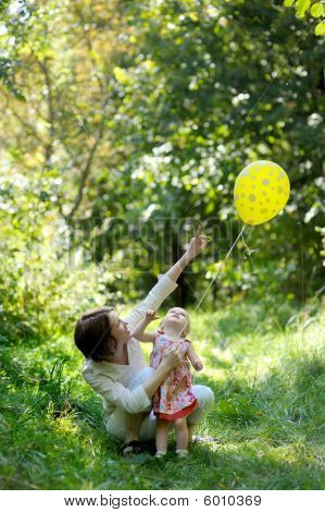 Young Mother And Her Little Baby Looking At The Balloon
