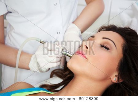 Woman getting laser face treatment in medical spa center, skin rejuvenation concept