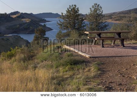 Picnic Table On Shore Of Mountain Reservoir