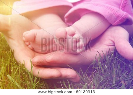 Baby feet in mother's hands outside in grass