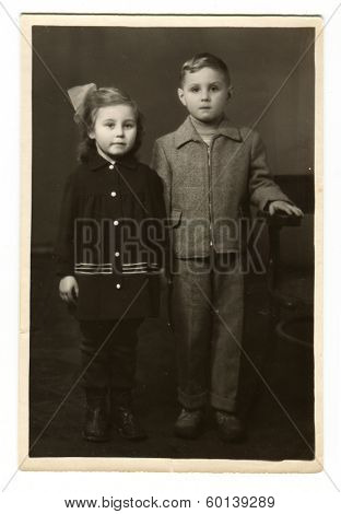 MOSCOW, USSR - CIRCA 1960s: An antique photo shows studio portrait of a little boy and girl - brother and sister