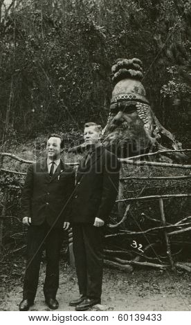 YALTA, USSR - CIRCA 1907: An antique photo shows studio portrait of two man in the park near the wooden sculpture Russian hero