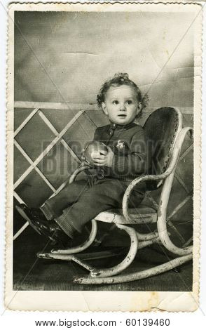 KURSK, USSR - CIRCA 1970s: An antique photo shows portrait of a little boy Kinky little boy sitting in a rocking chair