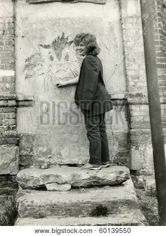 VORONEZH, USSR - CIRCA 1986: An antique photo shows portrait of girl drawing a cat on the wall of an old building