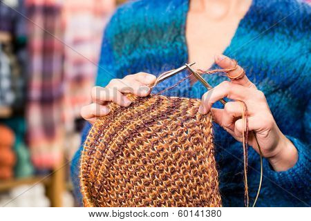 Young woman or saleswoman in knitting shop showing or explaining how to knit with circular needle