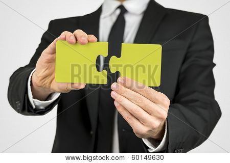 Man Holding Two Pieces Of A Yellow Puzzle