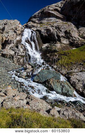 Waterfall flowing from Ala-Kul lake. Kyrgyzstan
