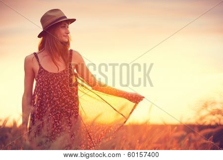 Beautiful woman in golden field at sunset, Fashion lifestyle, Vibrant color, Backlit warm tones