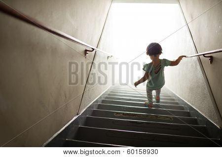 Little girl walking down stairs into white