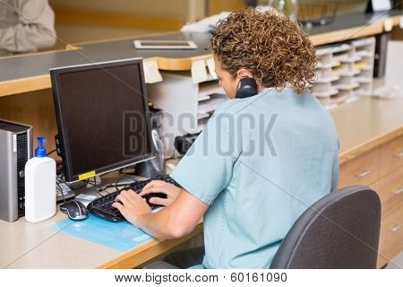 Rear view of female nurse answering telephone while working on computer at hospital reception