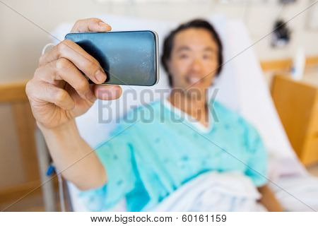 Mature male patient taking self portrait through mobile phone in hospital