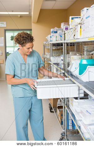 Female nurse arranging container in storage room of hospital