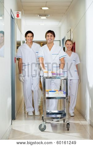 Portrait of confident lab technicians with medical cart walking in hospital corridor