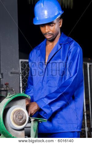 factory worker operating a grinding machine