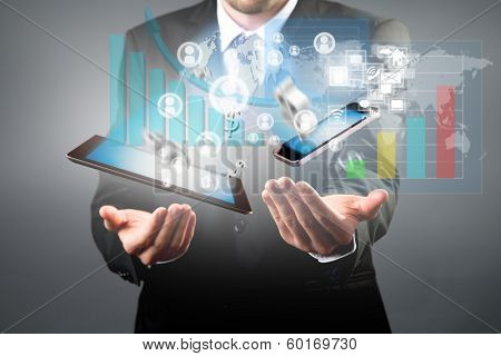 Business concept with manager holding tablet and smart phone. Virtual icons around