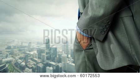 Close up of businessman standing on top viewing at city