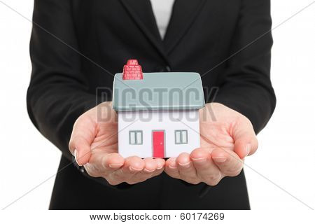 New Home and house owner concept. Woman holding a model house. Conceptual of home insurance and protection or real estate agent selling houses. Isolated on white background.