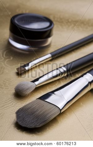 professional costmetic brushes on a gold surface