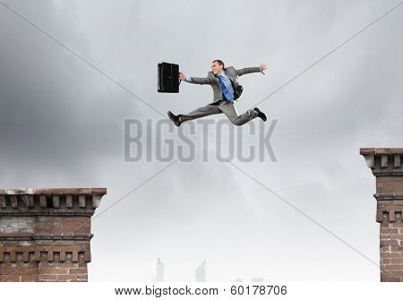 Young businessman jumping over gap. Risk concept