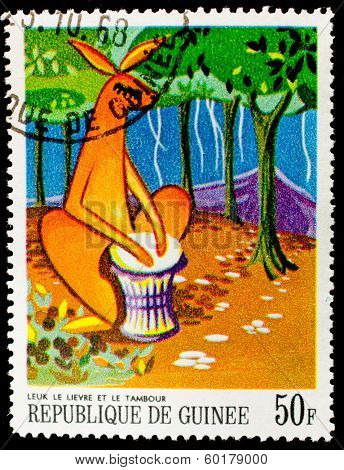 GUINEA - CIRCA 1968: A stamp printed in Guinea shows a kangaroo playing on an african musical instrument in the forest , circa 1968.