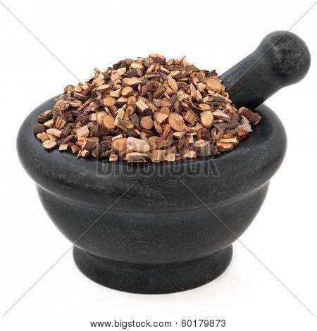 Cinnamon twig chinese herbal medicine in a black stone mortar with pestle over white background. Gui zhi.