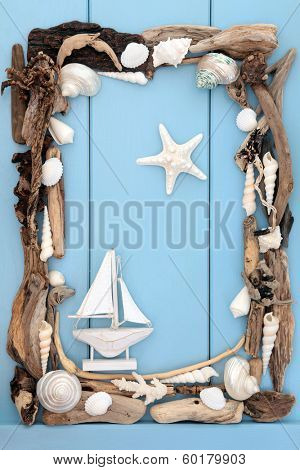 Sea shell and driftwood with small decorative boat forming an abstract border over wooden blue background.