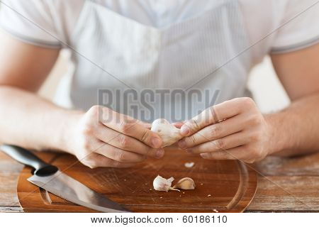 cooking and home concept - close up of male hands taking off peel of garlic on cutting board