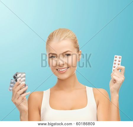 health, medicine, diet and pharmacy concept - young woman with variety of pills