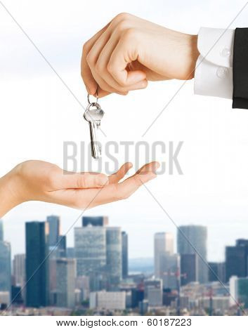 real estate and banking concept - close up of man hand passing house keys to woman