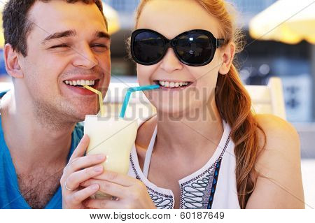 Romantic couple sharing a cocktail