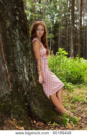 Young Woman Standing In A Tree Trunk