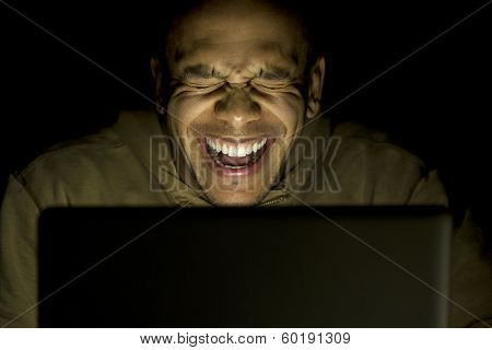 Man laughing at his laptop at night