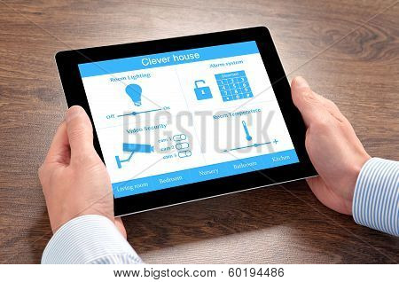 Businessman Holding A Tablet Computer With System Clever House