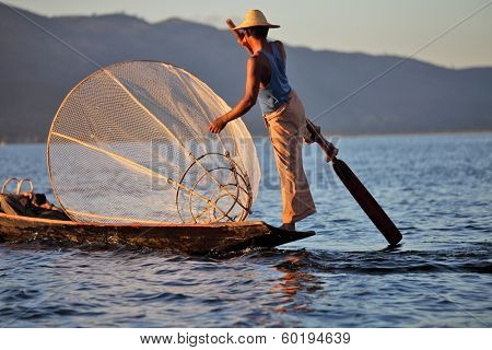 INLE LAKE, MYANMAR � DECEMBER 12, 2013: Fishermen at Inle Lake, Shan State, Myanmar Intha people possess the leg-rowing style and the unique coop-like fishing equipment