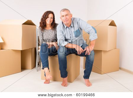 Happy mature couple unpacking boxes in their new home