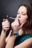 image of cigarette lighter  - Beautiful young woman is smoking cigarette on black background - JPG