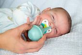 picture of snot  - Mother using bulb syringe to clean unhappy infant baby - JPG