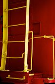 image of caboose  - A bright yellow steel ladder on a bright red vintage train caboose - JPG