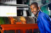 pic of heavy equipment operator  - African american printing machine operator standing next to a plastic bag printing press - JPG