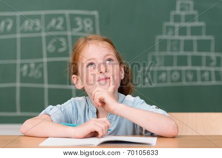 Little Girl Smiling As She Sits Thinking In Class