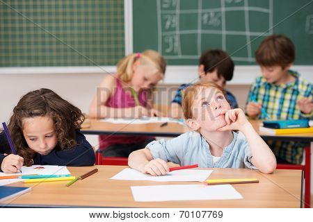Young Girl Sitting Thinking In Class At School