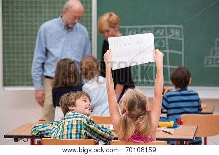 Little Girl Holding Up A Sheet Of Paper In Class