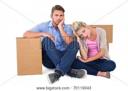 Unhappy young couple sitting beside moving boxes on white background
