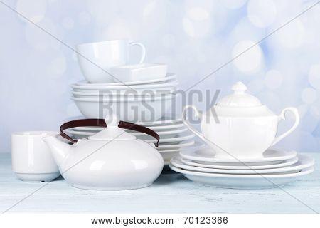 White crockery and kitchen utensils, on light background