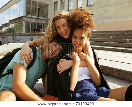cute group teenages at the building of university with books huggings