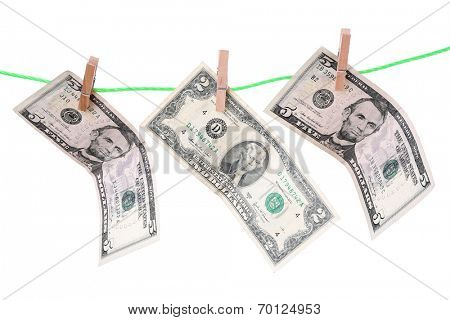Dollar bills hanging on rope attached with clothes pins. Money-laundering concept. Isolated on white background.