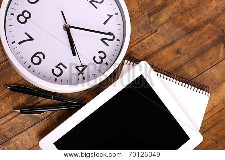 Tablet, cup of coffee, notebook and clock on wooden background