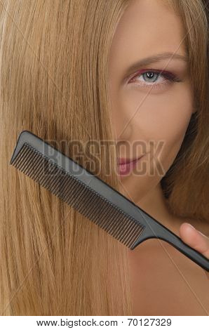 Young Woman Holding Comb Straightened Hair